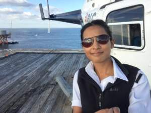 Anusha, a helicopter pilot wearing Bigatmo Tropo photochromic sunglasses standing next to her helicopter on the oil rigs